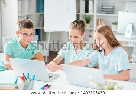 Three schoolmates pointing at something curious on laptop display Stock photo © pressmaster