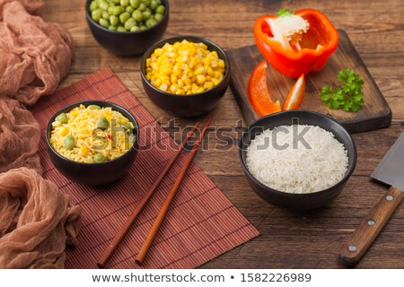 black bowl with boiled organic basmati vegetable rice with wooden chopsticks on brown placemat with stock photo © denismart