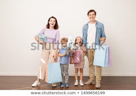 Laughing young parents with paperbags and their cheerful son and daughter Stock photo © pressmaster