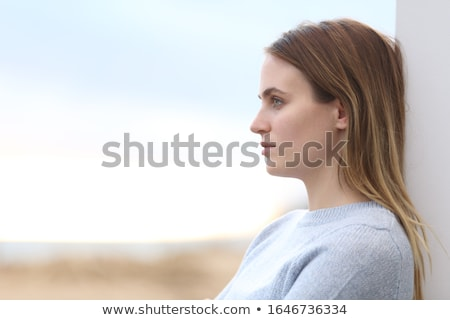 Side view of thoughtful young woman standing on beach in the sunshine Stock photo © wavebreak_media