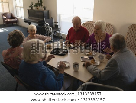 High angle view of group of senior friends having breakfast on dining table at home Stock photo © wavebreak_media