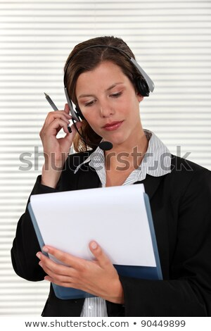 Woman adjusting her headset and holding a clipboard Stock photo © photography33