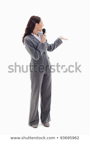 Businesswoman announcer speaking in a microphone and looking behind against white background Stock photo © wavebreak_media
