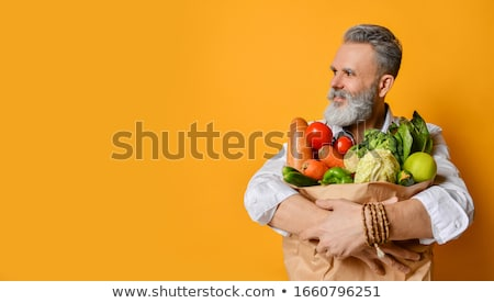 Happy man holding grocery shopping bag. Stock photo © RAStudio