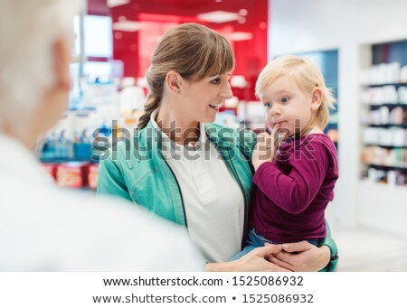mother with daughter in pharmacy at the counter stock photo © kzenon