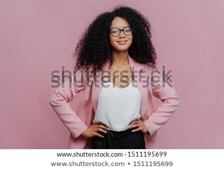 Waist up shot of satisfied dark skinned female office worker keeps hands on her slim figure, has hap Stock photo © vkstudio