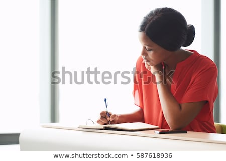 african student woman writing to diary or notebook Stock photo © dolgachov