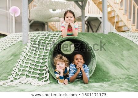 Friendly intercultural little kids having rest on play area at leisure center Stock photo © pressmaster
