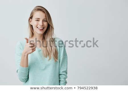 smiling young woman in shirt showing thumbs up Stock photo © dolgachov