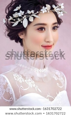Young woman in dress in oriental style and a wreath of fresh flowers lilies isolated on white backgr Stock photo © Lady-Luck
