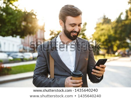 Portrait of businesslike men in suits using smartphone while wal Stock photo © deandrobot