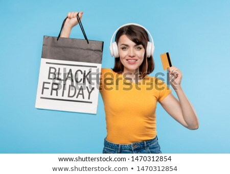 Young smiling female shopaholic in casualwear and headphones Stock photo © pressmaster