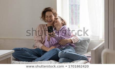 Lovely teenage girl enjoys online communication, holds modern cell phone, checks email box, connecte Stock photo © vkstudio