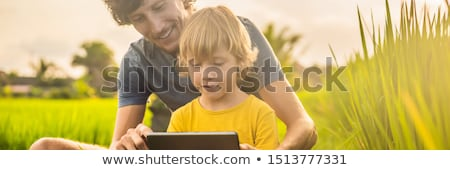 Dad and son sitting on the field holding tablet. Boy sitting on the grass on sunny day. Home schooli Stock photo © galitskaya
