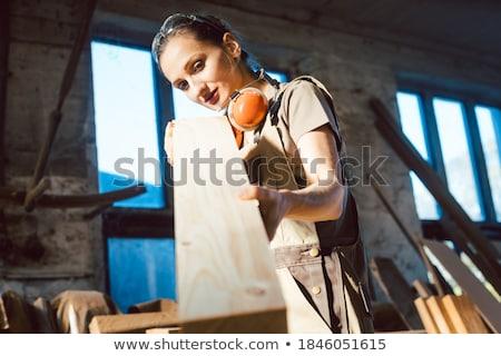 Beautiful woman carpenter checking quality of a plank Stock photo © Kzenon