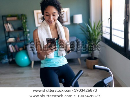 Stock photo: Woman using cycling machine to stay fit