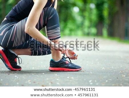 Sports woman in park outdoors tie her laces. Stock photo © deandrobot