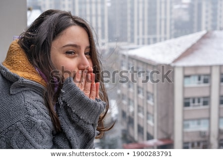 Cute girl looking at the cityscape while snowing Stock photo © konradbak