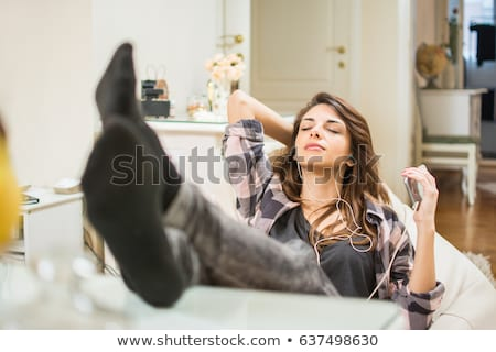 Smiling woman with legs up on couch in living room Stock photo © Lopolo
