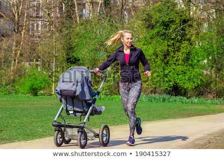 A Young mother jogging with a baby buggy Stock photo © Lopolo