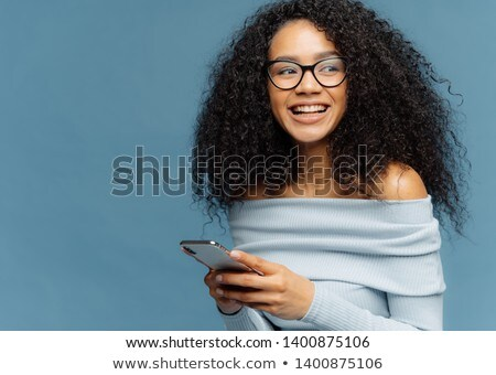 Delighted dark skinned woman with crisp hair, looks away, wears spectacles, uses modern cell phone f Stock photo © vkstudio