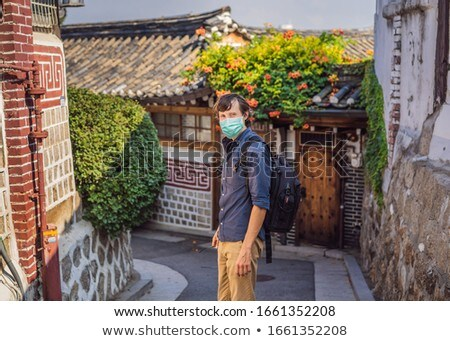 Young man tourist in medical mask in Bukchon Hanok Village is one of the famous place for Korean tra Stock photo © galitskaya