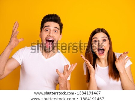 young casual couple with hands in the air screams Stock photo © feedough