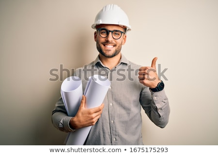 architect in helmet with blueprints showing ok Stock photo © dolgachov