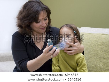 mother using inhaler with her asthmatic daughter Stock photo © Lopolo