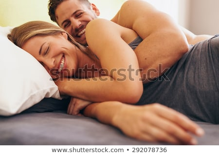 man waking his sleeping wife up in bed at home Stock photo © dolgachov