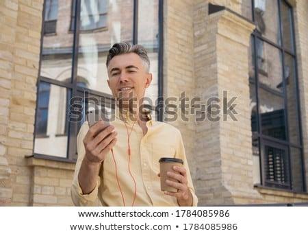 Kép üzletember mobiltelefon fülhallgató szemüveg sétál Stock fotó © deandrobot