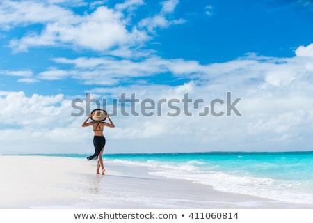 Luxury beach travel vacation swimwear woman relaxing walking on white sand in beachwear cover-up. As Stock photo © Maridav