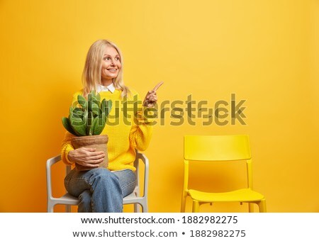 Photo of relaxed young woman dressed in warm knitted clothes, lies on comfortable sofa, enjoys domes Stock photo © vkstudio