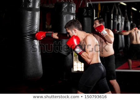A Boxers doing some training on a punching bag at a gym Stock photo © Lopolo
