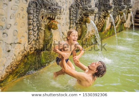 Dad and son travelers in hot springs banjar. Thermal water is released from the mouth of statues at  Stock photo © galitskaya