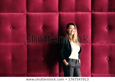 Young Business Woman Standing Against Burgundy Wall Panels Stock photo © diego_cervo