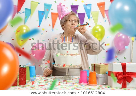 senior female blows out candles on a cake Stock photo © meinzahn