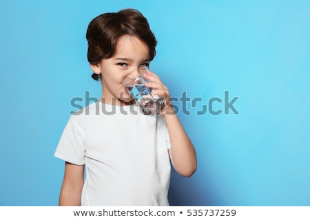 sedento · menino · potável · garrafa · isolado · branco - foto stock © meinzahn