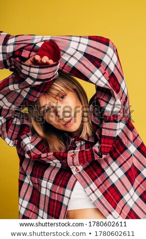 Woman in shorts and checkered top poses in studio Stock photo © dash