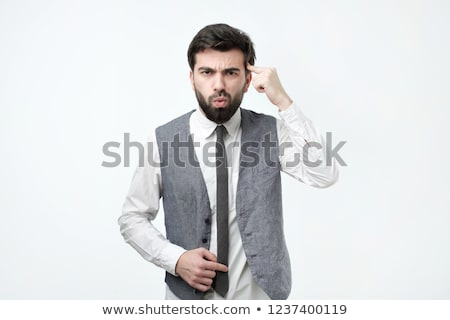 Angry man gesturing with his finger against temple Stock photo © RAStudio