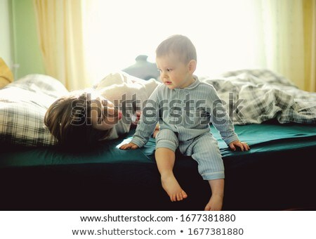Stock photo: A baby and his brother on bed having fun
