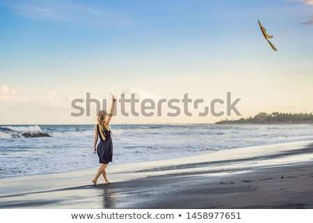 A young woman launches a kite on the beach. Dream, aspirations, future plans Stock photo © galitskaya