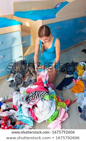 Beautiful teenage girl folding her messy clothes in a her bedroom Stock photo © Len44ik
