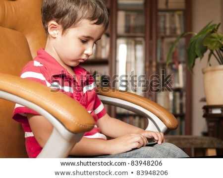 Little boy play smartphone game in leather chair Stock photo © pekour