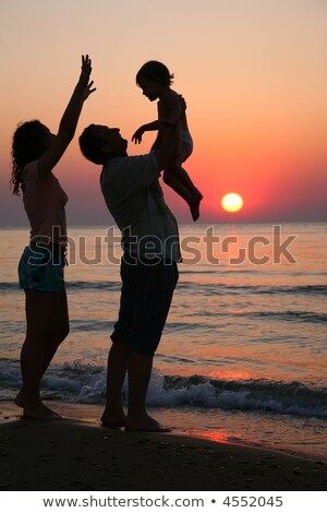 Stock photo: Mummy with daughter and grandfather on sunset at sea