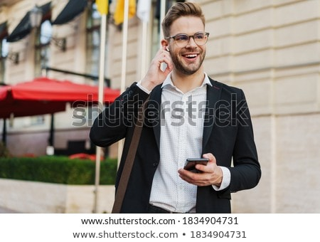 Image of joyful businessman using cellphone and earphones Stock photo © deandrobot