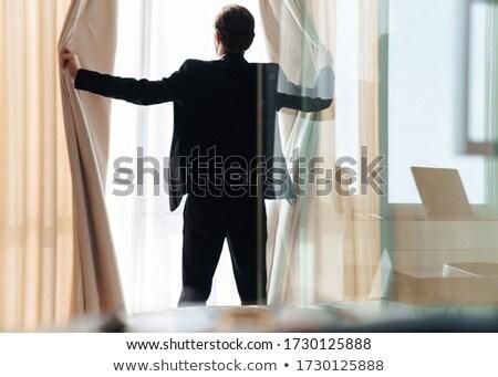 Photo of caucasian brunette businessman pulling back curtain Stock photo © deandrobot