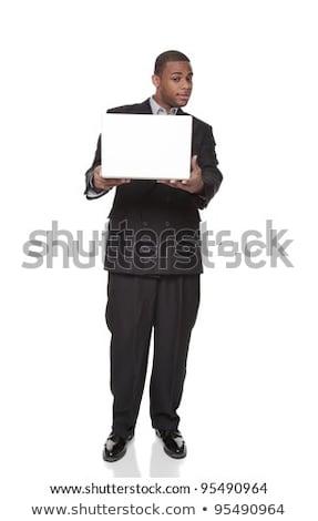 African American businessman looking warily at laptop computer Stock photo © dgilder