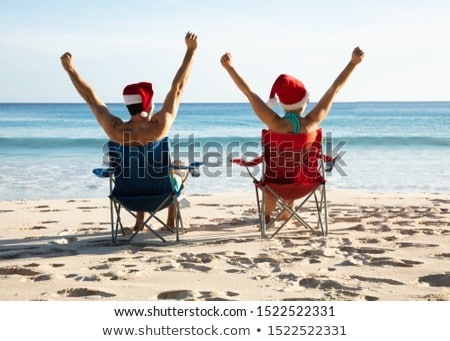 Young Couple Sitting On Chairs Raising Their Arms Stock photo © AndreyPopov