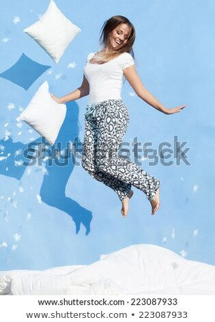 Heureux femme bleu sautant oreiller amusement Photo stock © dolgachov